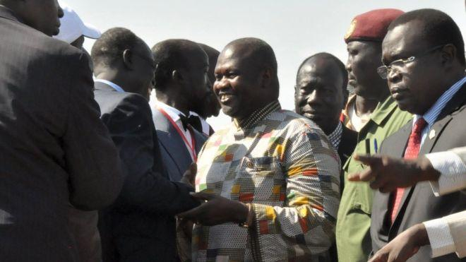 Riek Machar (c) was greeted at the airport before heading to be sworn in as vice-president