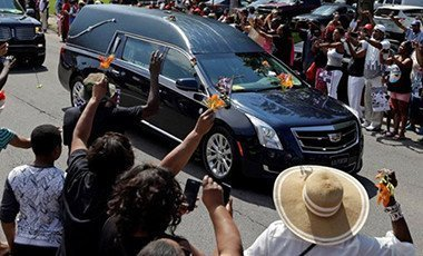 Well-wishers have been throwing flowers onto the hearse