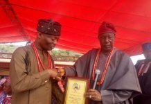 Wale Ojo-Lanre receiving an award from an Ogidi Community chief